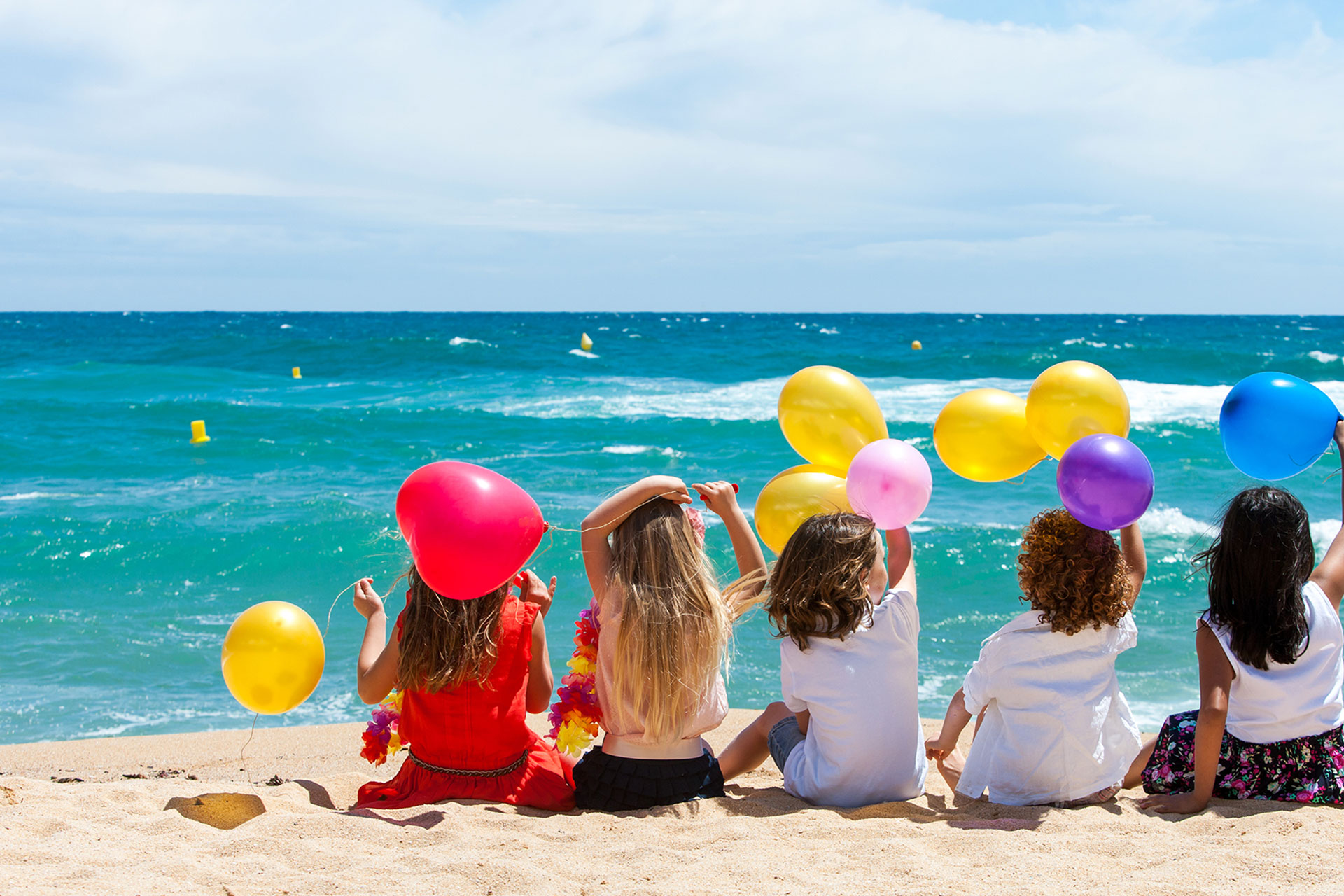 Kids on the beach with balloons